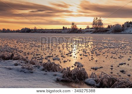 The Sun Rises Over The Frozen River At The Rural Finland. The Frost Has Formed Spiked Formations Ove