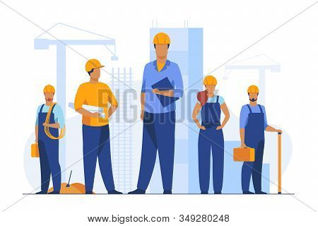 Construction Team Working On Site. Builders, Engineers, Architects In Helmets And Overalls Holding B