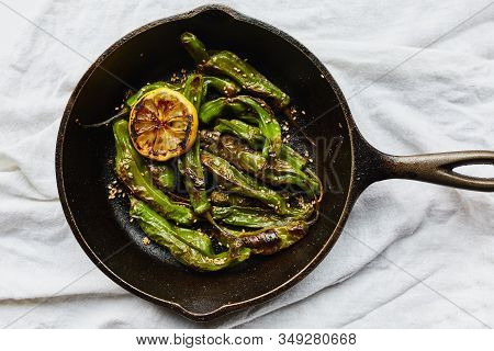 Sesame Blistered Shishito Peppers With Lemon, Sesame Oil And Sesame Seeds Cooked In A Cast-iron Pan