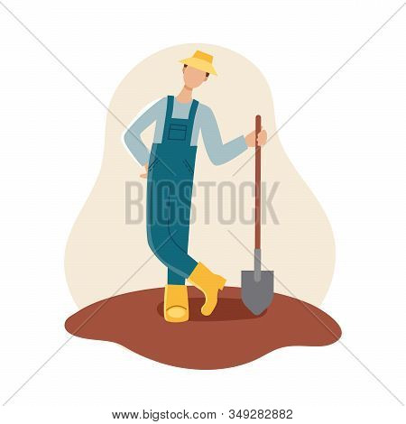 A Male Gardener In A Yellow Hat, Boots, And Blue Robe Holds A Shovel. Spring Planting.gardening And