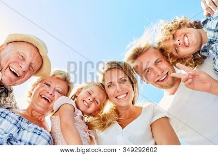 Happy three generation family with grandparents and children in the sun