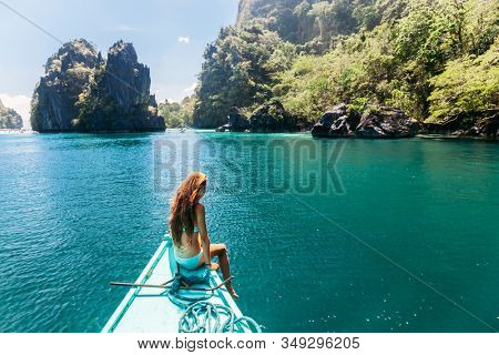 Back view of the young girl relaxing on the boat and looking at the island. Travelling tour to lagooin in Asia: El Nido, Palawan, Philippines.