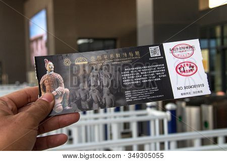 Xian, China - December 29, 2019: Asian Hand Holding Entrance Ticket In Front Of The Entrance Terraco