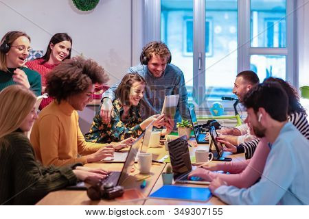 Young teamwork using computer in the apartment. Millennial people working together at new project. Youngers youtubers looking cute videos. Technology, influencer, marketing and job concept - Image