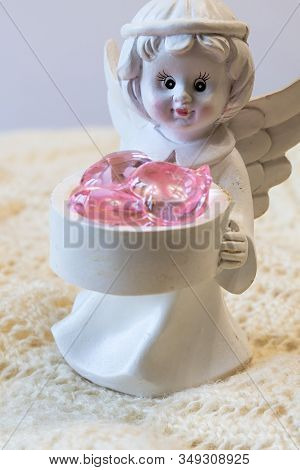 White Ceramic Figurine Of An Angel Holding A Basket With Pink Hearts, On A Light Background. Angel F