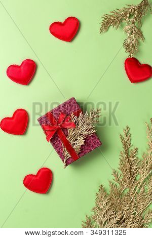 Golden Branch With Gift Box And Hearts On A Green Background. Copy Space.