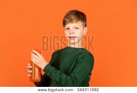 Water Balance. Small Child Drink Juice Orange Background. Little Boy Enjoy Drinking Fruit Juice. Jui