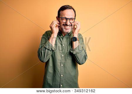 Middle age hoary man wearing casual green shirt and glasses over isolated yellow background covering ears with fingers with annoyed expression for the noise of loud music. Deaf concept.