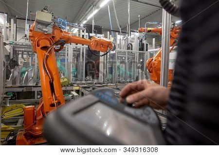 Man Programming Robot In Automotive Industrial, Professional Programmer, Industry Concept