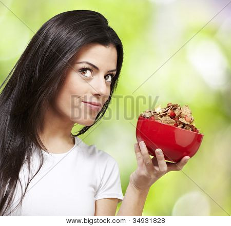 woman holding a delicious red breaksfast bowl against a nature background