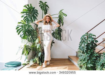 Full-length Indoor Portrait Of Smiling Curly Woman In Long White Skirt And Stylish Glasses. Cheerful