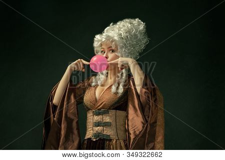 Pink Bubble Gum. Portrait Of Medieval Young Woman In Brown Vintage Clothing On Dark Background. Fema
