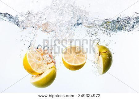 On White Background, Lemon And Apple Are Cut In Half, Thrown Into Water And Splashes Fly From It