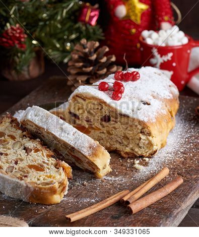 Traditional European Stollen Cake With Nuts And Candied Fruit On A Wooden Board, Close Up