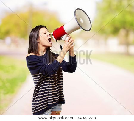 portrait of a young woman screaming with a megaphone at a park