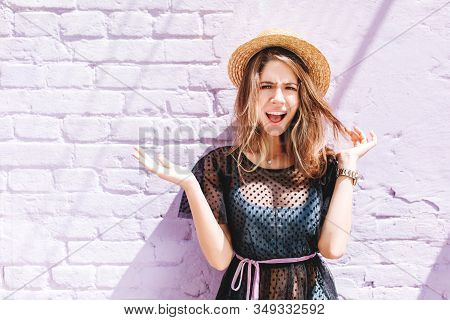 Attractive Girl Wears Summer Hat And Wristwatch Posing With Palms Up And Incredulous Face Expression