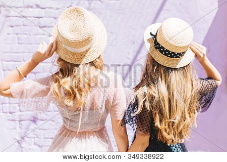 Outdoor Close-up Portrait From Back Of Fair-haired Curly Sisters Spending Time Together In Sunny Mor