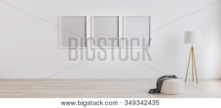 Bright Room Interior With Three Empty Frames For Mockup With Wooden Floor Lamp, White Pouf And Woode