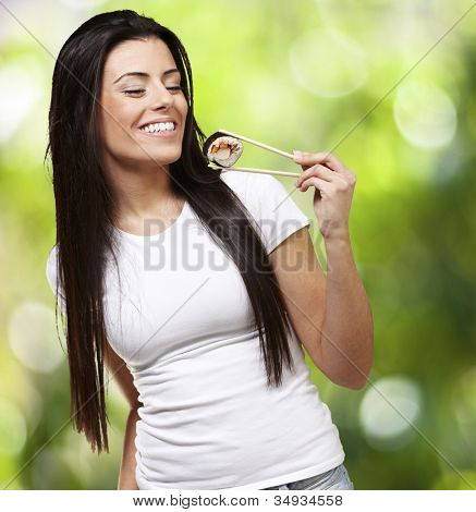 young woman eating a sushi piece against a nature background