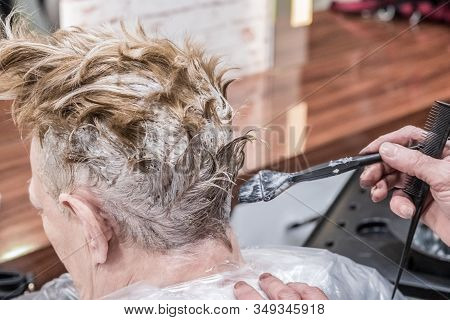 Professional Hairdresser Dying Client's Hair In Beauty Salon