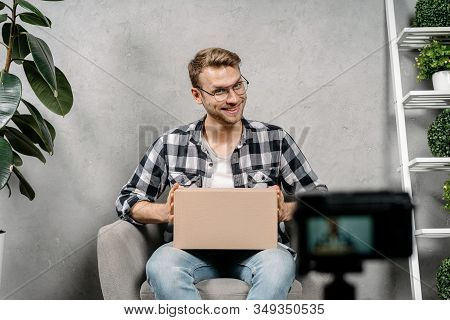 Cheerful Young Adult Social Influencer Holding Carton Box In Hands, Creating Video Content For Media