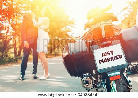 Wedding, Newlyweds. The Back Of A Bike With A Sign Just Married. A Man And A Woman In Wedding Dresse