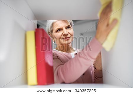 people, housework and housekeeping concept - happy senior woman with dusting cloth cleaning rack at home