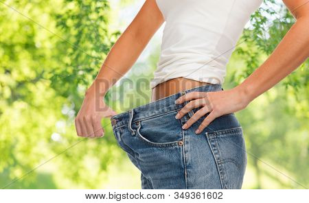 weight loss, slimming and diet concept - close up of woman in oversize jeans showing her slim waist over green natural background