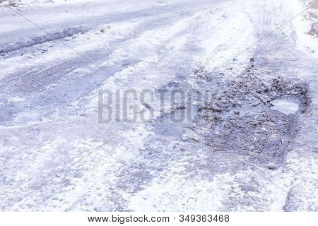 The Bad Asphalt Winter Road Or Way With Ice, Snow, Puddles, Pools, Mud And Slush