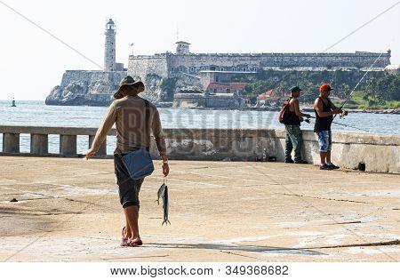 Havana, Cuba - 25 July 2018: Fisherman In Havana Cuba Walking On The Malecan With The Fish He Just C