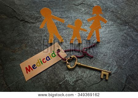 Paper Family Of Three With Gold Key And Colorful Medicaid Tag