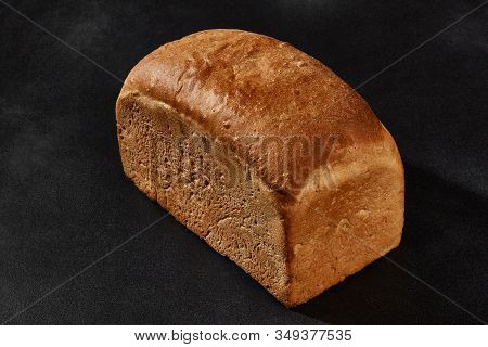 Whole Loaf Of Fresh, Palatable Baked White Bread Against Black Background With Copy Space. Close-up