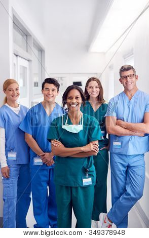 Portrait Of Smiling Multi-Cultural Medical Team Standing In Hospital Corridor