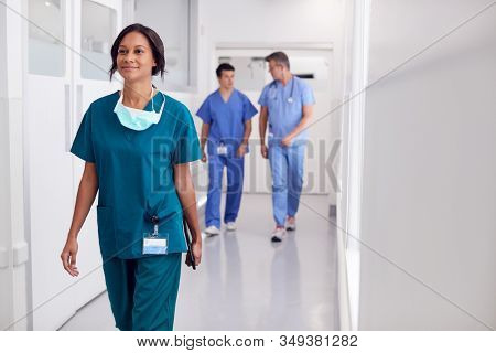 Female Doctor Wearing Scrubs In Hospital Walking Along Corridor Holding Digital Tablet