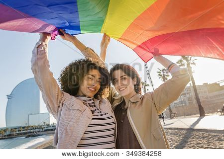 Smiling Young Homosexual Couple Of Women Waving The Rainbow Flag, Symbol Of The Struggle For Gay Rig
