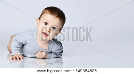 Portrait Of Little Baby Boy Toddler In Grey Casual Jumpsuit Lying On Floor And Smiling Over White Wa