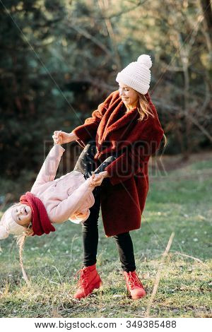 Mother And Daughter Have Fun And Frolic While Walking In The Forest.