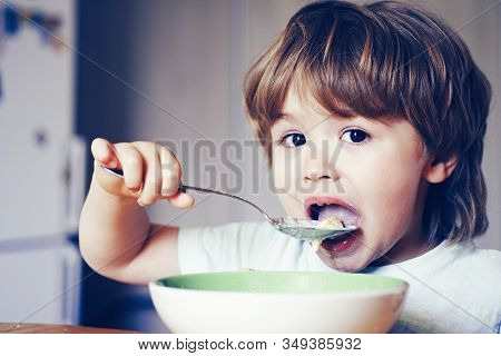 Hungry Little Boy Eating. Cheerful Baby Child Eats Food Itself With Spoon. Tasty Kids Breakfast. Bab