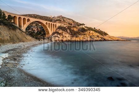 Long Exposure Of Scenic Sunset At Calanque Des Eaux Salees Or Salt Water Rocky Inlet With Pebble Bea