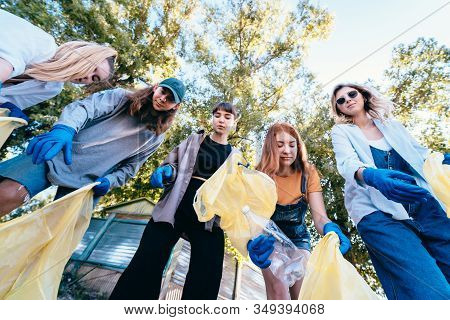Group Of Activists Friends Throw A Lot Of Garbage In A Bag. Bottom-up Shooting