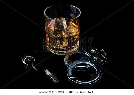 Whiskey on the rocks with handcuff and car key against a black background