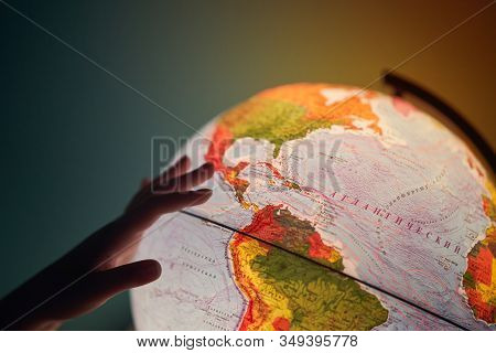 A Girl Turns The Globe. Glowing Globe In The Dark. Selective Focus. Planet Earth. Globe With Russian