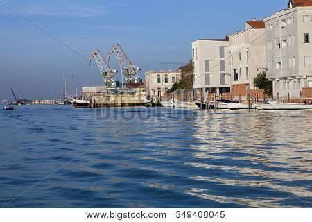 Shipping Cranes Loom In The Distance In Giudecca