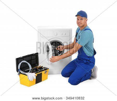 Plumber Repairing Washing Machine On White Background