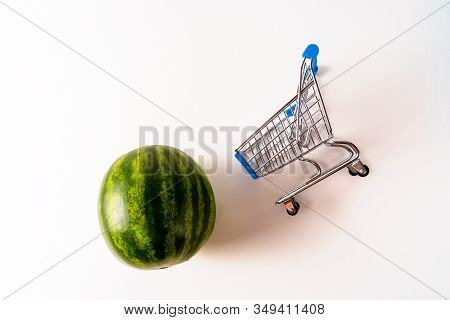 Empty Shopping Trolley And Seedless Watermelon Isoalted On White Background. Copy Space For Text Or