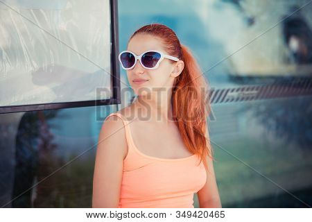 The Young Redhead Woman Sitting At The Bus Stop She Expects The Bus Outdoors. Stylish Girl In Casual