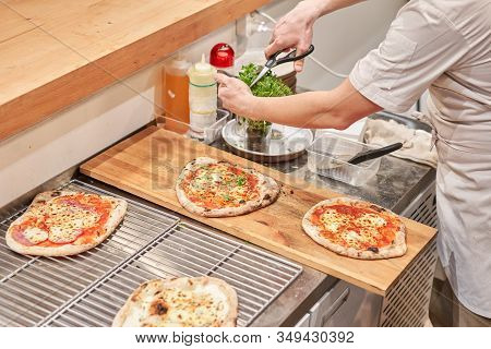 Italian Kitchen And Cooking Concept. Chief With A Pizza Cutter Cutting Pizza To Pieces At Neapolitan