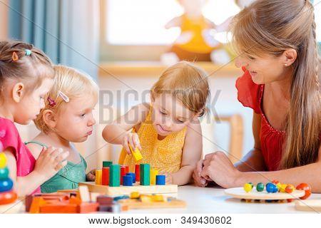 Group of children and teacher playing practical games in kindergarten