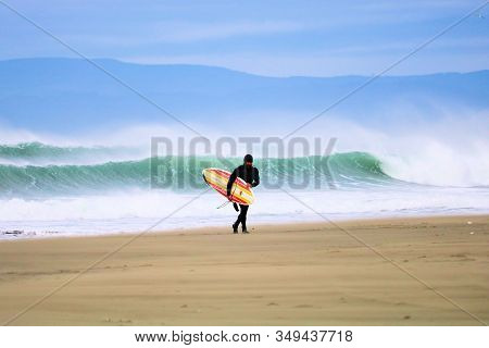 January 16, 2020 In Eureka, Ca:  Person Carrying Their Surfboard After Surfing Large Waves During A