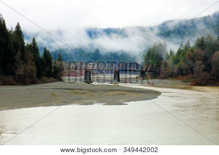 Rain Falling Over The Eel River Including A Historic Railroad Bridge With Trestles Surrounded By Lus
